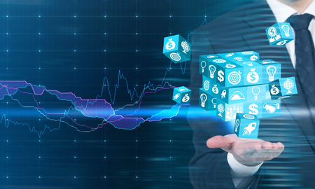 cube puzzle: Businessman holding digital cube puzzle in palm with business chart in the background
