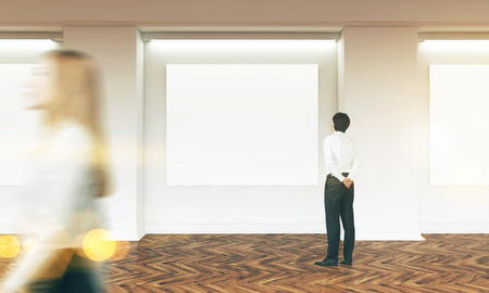 blank canvas: Gallery interior with several blank canvas hanging on wall and businesspeople passing by and looking. Toned image. Wooden flooring. Mock up, 3D Rendering
