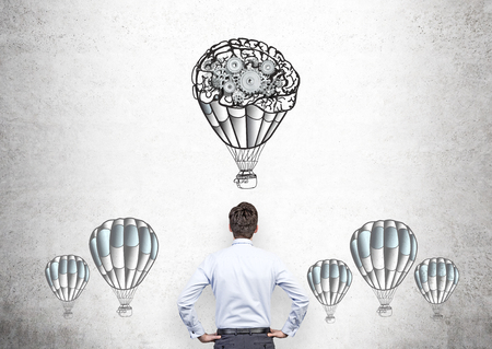 Businessperson looking at airballoons and gears sketch on concrete wall Stock Photo