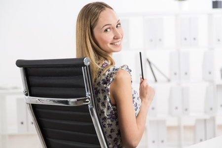 sideview: Sideview of smiling young girl sitting on sviwel-chair in office Stock Photo