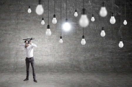 cement solution: Idea concept with businessman aiming at lightbulbs on concrete background Stock Photo