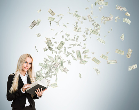 money flying: Businesswoman with money flying out of book on light grey background