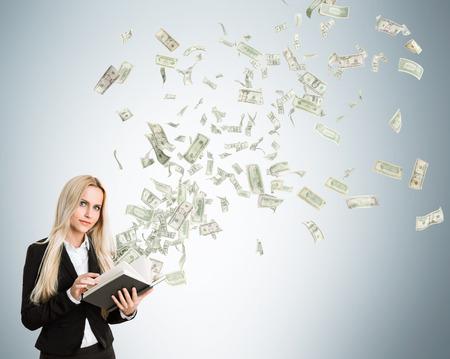dinero volando: Empresaria con el dinero volando de libro sobre fondo gris claro Foto de archivo