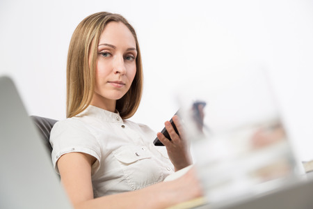 sideview: Lady using phone at desk. Sideview