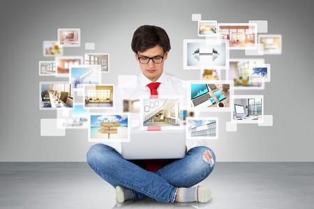 Jeune homme utilisant son ordinateur portable pour le site de surf. Différentes icônes avec des images apparaissant sur l'écran