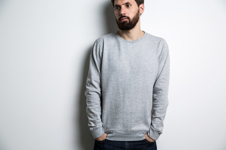 Young man in long sleeved sweatshirt on light grey background