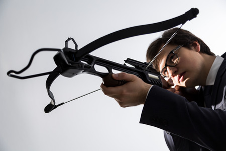 arbalest: Businessman aiming with crossbow on light background Stock Photo