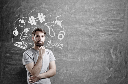 sporting goods: Thoughtful man with sporting goods sketch on concrete wall Stock Photo