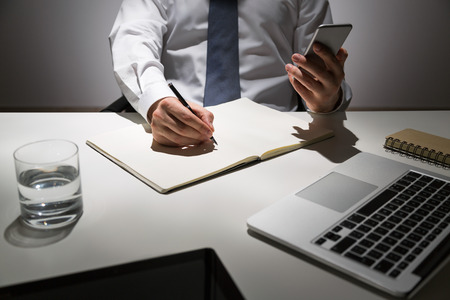 Businessman at office table copying infromation from phone to copybook
