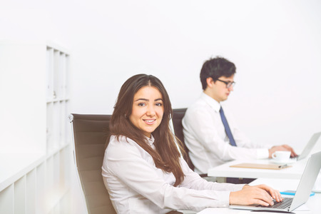 sideview: Sideview of smiling businesswoman and concentrated businessman working in office