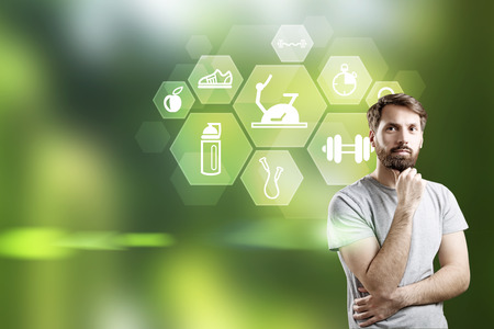 Thougtful bearded businessman and icons with sporting goods on green background