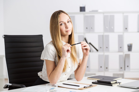 executive apartment: Woman sitting at desk with items in office