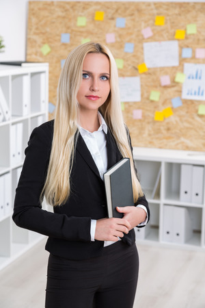 closed book: Businesswoman with closed book. Office at background. Concept of work. Stock Photo