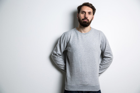 Young bearded man in grey shirt with long sleeves on light grey background. Mock up Stock Photo