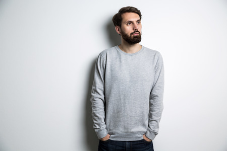 Young male in long sleeved sweatshirt on light grey background. Mock up Stock Photo