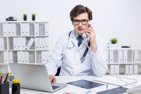 nhs: Young caucasian doctor using laptop and having a telephone conversation at his office desk with shelves in the background