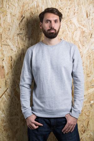 Man in grey sweatshirt on textured light brown background. Mock up