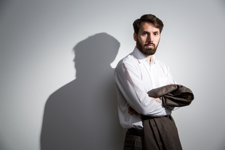shadow man: Man in white shirt with his suit jacket in hands standing against wall with shadow