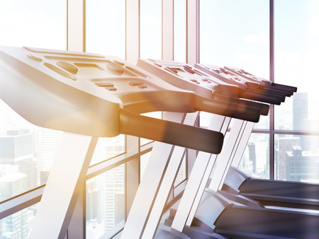toned: Closeup of treadmills in room with windows, New York city view and sunlight. Toned image, 3D Rendering