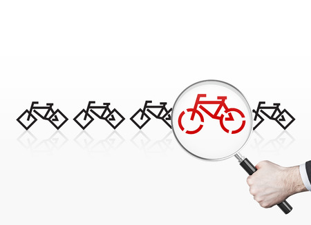 nonpolluting: Businessman looking at red bicycle drawing through magnifying glass trying to choose the most suitable one. Stock Photo