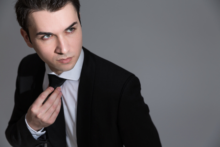 looking away from camera: Handsome caucasian businessman looking away from the camera on light grey background
