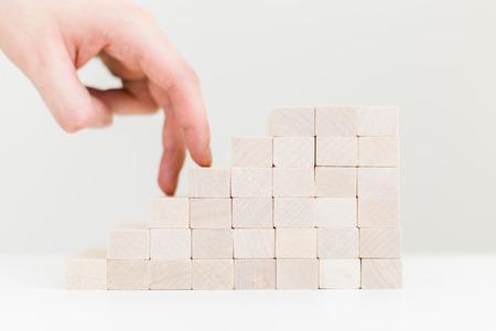 wooden block: Financial growth concept with businessman fingers climbing wooden block ladder