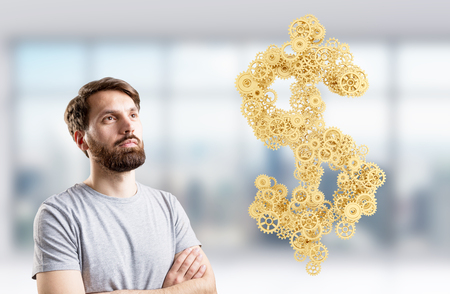 signos de pesos: Teamwork concept with golden dollar sign made of gears next to thoughtful male