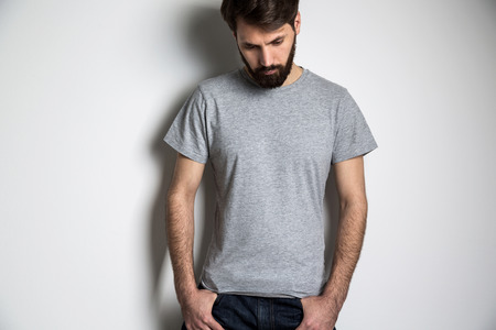 Bearded man in grey shirt with short sleeves looking down on grey background. Mock up Stock Photo
