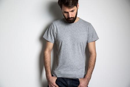 Uomo barbuto in camicia grigia a maniche corte guardando verso il basso su sfondo grigio. Modello Archivio Fotografico