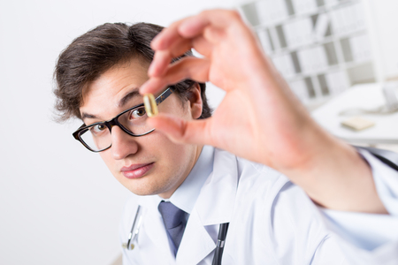 raised eyebrows: Young handsome doctor with raised eyebrows holding yellow pill Stock Photo