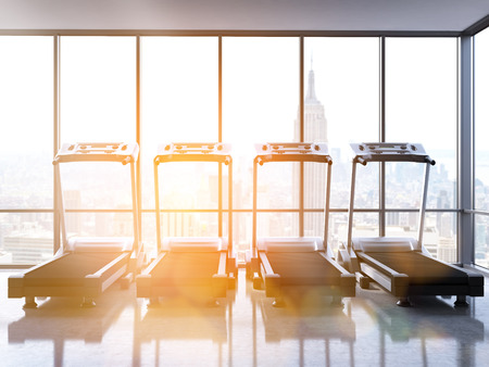 rearview: Rearview of four treadmills in room with concrete floor,  windows with New York city view and sunlight. Toned image, 3D Rendering Stock Photo