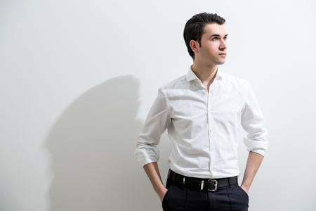 formally: Formally dressed caucasian male with hands in pockets standing against white wall with shadow