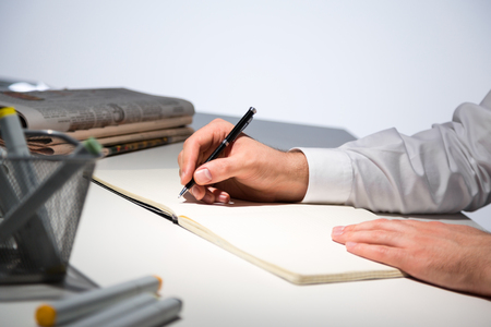 sideview: Sideview of businessperson hands writing in journal on office desk