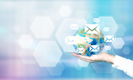 businesspersons: Email network around globe in businesspersons palm on abstract blue background.