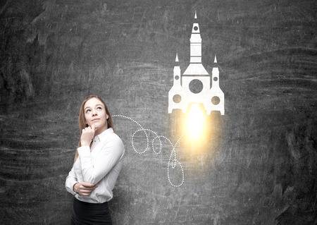 businesswoman standing: Startup concept with thinking businesswoman standing against chalkboard with rocket sketch Stock Photo