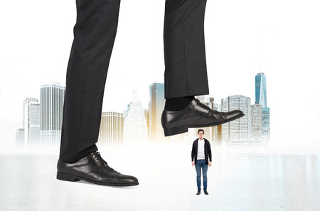 violence in the workplace: Abuse of authority concept with huge businessman foot stepping on a male miniature on New York city background