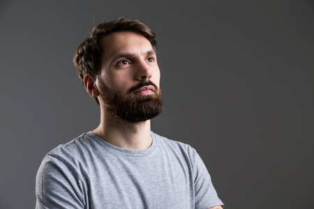 looking away from camera: Portrait of bearded man in grey shirt looking away from the camera on dark grey background Stock Photo