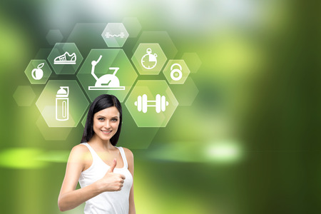 Pretty caucasian female showing thumbs up and icons with sporting goods on green background Stock Photo