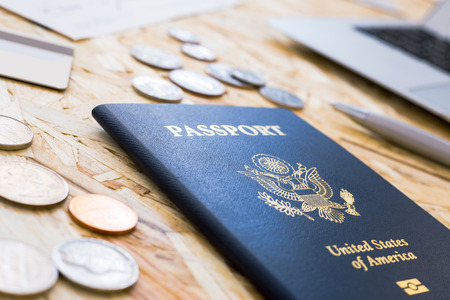 wood chip: Closeup of american passport, dollar coins, laptop and pen on wood chip table Stock Photo