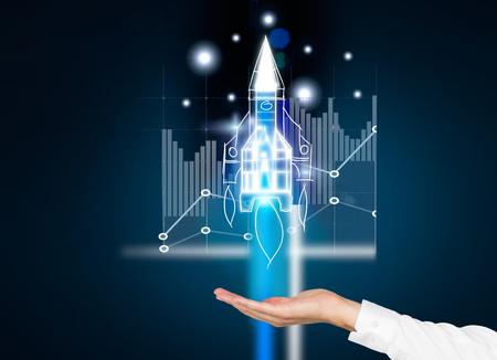 Startup-Konzept mit Geschäftsmann Hand hält Digitalraketenschiff mit Business-Diagramm auf dunkelblauem Hintergrund