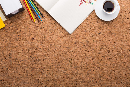 Topview of cork table with blank notepad, coffee cup, pencils and other items. Mock up