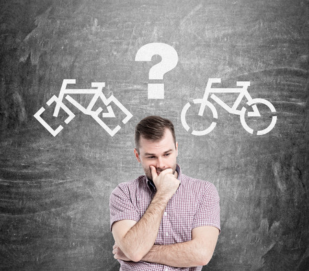 nonpolluting: Caucasian male standing against chalkboard with bicycle sketches, thinking which one to choose.