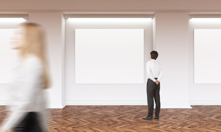 canvas on wall: Gallery interior with several blank canvas hanging on wall and businesspeople passing by and looking. Wooden flooring. Mock up, 3D Rendering Stock Photo
