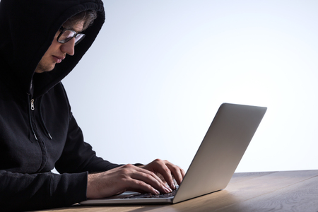 cyber terrorism: Guy with black hood sitting at wooden desk and hacking computer