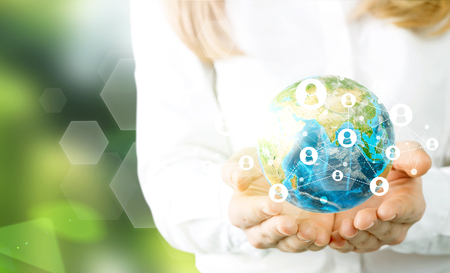 hands holding globe: Businesswoman hands holding globe with social networking system on green background.