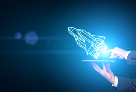 Businessman hands holding tablet with abstract rocket ship on blue background. Start up concept