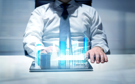 Businessperson in office using tablet with New York city hologram