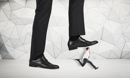 violence in the workplace: Abuse of authority concept with huge businessman foot stepping on a running male miniature with patterned concrete wall in the background Stock Photo