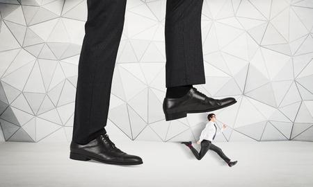 Misbruik van gezagconcept met reusachtige zakenmanvoet die op een lopende mannelijke miniatuur met gevormde concrete muur op de achtergrond stappen Stockfoto