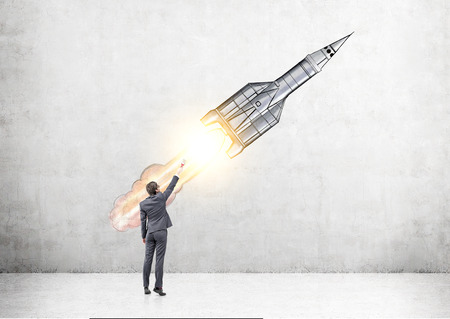 Start up concept with businessman drawing rocket sketch on concrete wall Stock Photo